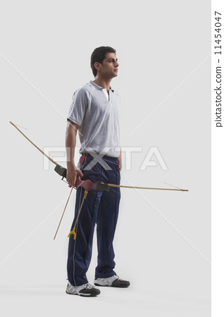 Young male archer standing with bow and arrow isolated over gray background 11454047