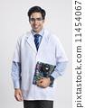 Portrait of confident male technician holding machine part against gray background 11454067