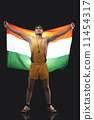 Proud young medalist with Indian flag standing against black background 11454317