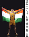 Full length of happy male medalist with Indian flag standing against black background 11454368