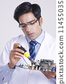 Young male technician working on machine part over gray background 11455035