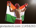 Happy male boxer looking up as he holds Indian flag isolated over black background 11456263
