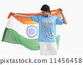Happy Indian hockey player looking at Indian flag isolated over white background 11456458