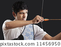 Close-up of young man aiming bow and arrow isolated over black background 11456950
