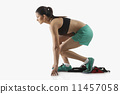 Profile shot of young female runner at starting block isolated over white background 11457058