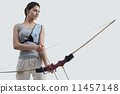 Young female archer with bow and arrow isolated over gray background 11457148