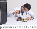 Young computer technician working on mother board against gray background 11457379