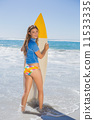 Fit smiling surfer girl standing on the beach with her surfboard 11533335