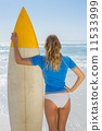 Blonde surfer holding her board on the beach 11533999