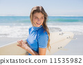 Fit smiling surfer girl on the beach with her surfboard 11535982