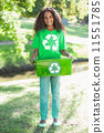 Young environmental activist smiling at the camera holding box 11551785