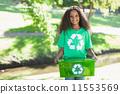 Young environmental activist smiling at the camera holding box 11553569