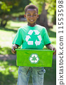 Young boy in recycling tshirt holding box 11553598