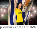 Composite image of excited football fan in brasil tshirt holding 11601692