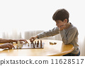 Boy playing chess with elderly man 11628517