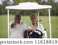 Senior African American couple driving golf cart 11628819