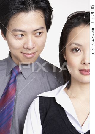 Close up of Asian businessman looking at Asian businesswoman 11629285