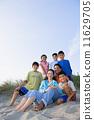 Portrait of Hispanic family sitting on beach 11629705
