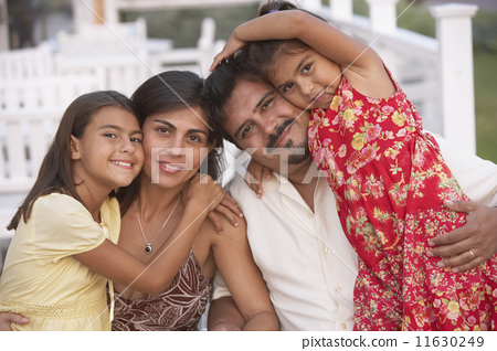 Hispanic family hugging on porch 11630249