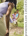 African sister and brother playing with mother in park 11631635