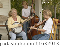 Mother and sons playing instruments together on porch 11632913