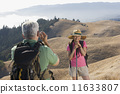 Senior man taking a picture of his wife on a hike 11633807