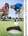 Multi-ethnic men looking at golf ball 11634214