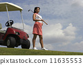 Hispanic woman standing next to golf cart 11635553