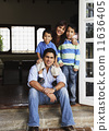 Hispanic family hugging in doorway 11636405