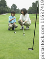Mother teaching son to play golf 11637419