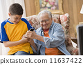 Young boy and his grandfather fighting over the remote control 11637422