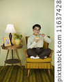 Nerdy Asian man eating in chair 11637428