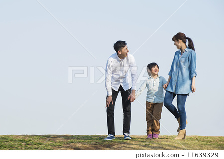Parent and child walking under blue sky 11639329