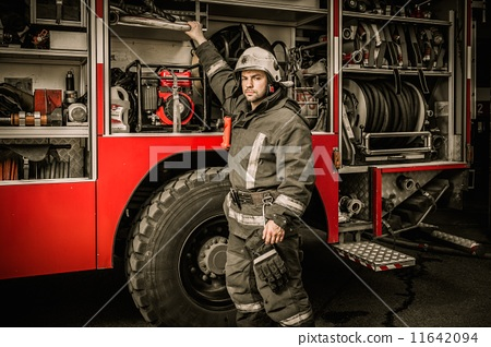 Stock Photo: Fireman taking equipment from firefighting truck
