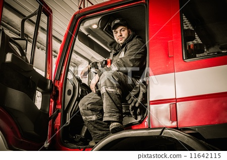 Stock Photo: Fireman behind steering wheel of a firefighting truck
