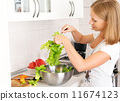 happy woman housewife preparing salad in the kitchen 11674123