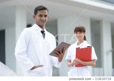 Portrait of successful medical doctor and nurse holding iPad tablet file in front of hospital 11810719