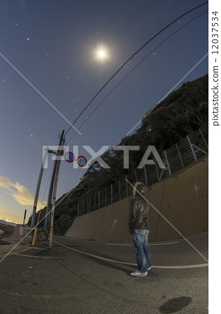 A man looking up at the moon and the stars 12037534