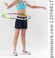 woman exercising with hula hoop 12056617