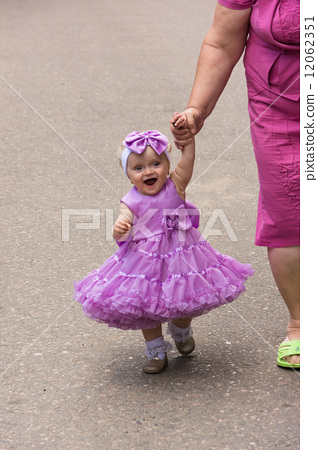 Beautiful little girl standing on the street in the model dress. 12062351