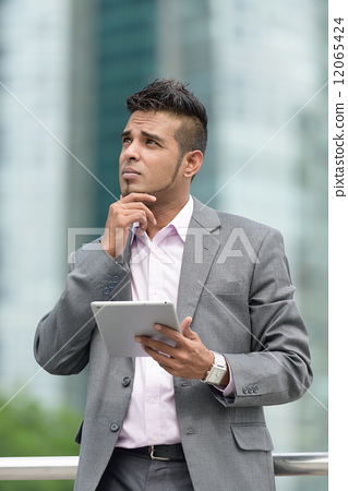One successful Malay business man with tablet iPad pointing in front of office building 12065424