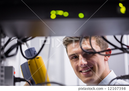 Smiling technician using digital cable analyzer on server 12107398