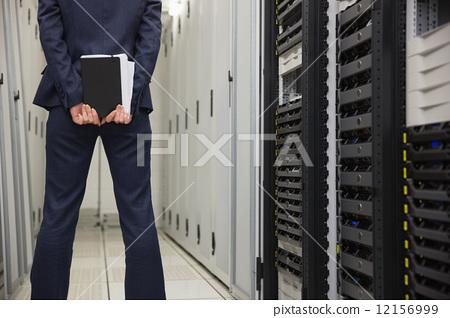 Technician standing in server hallway 12156999