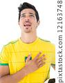 Brazilian football player in yellow singing to anthem 12163748