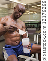 Body builder scooping up protein powder 12179299