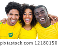 Happy brazilian football fans in yellow smiling at camera 12180150
