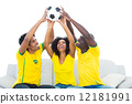 Happy football fans in yellow sitting on couch with ball 12181991