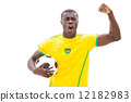 Excited brazilian football fan cheering holding ball 12182983