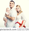 Happy young family with gift box over white background 12211726