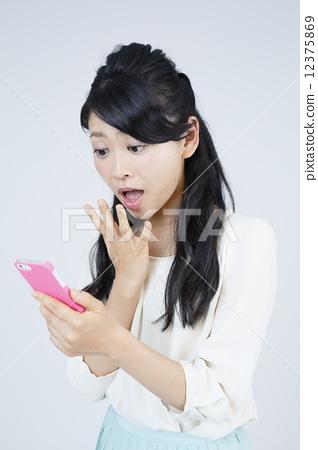 스마트 폰을 조작하는 젊은 여성 12375869